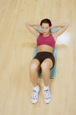Photo of young woman doing crunches on a floor mat