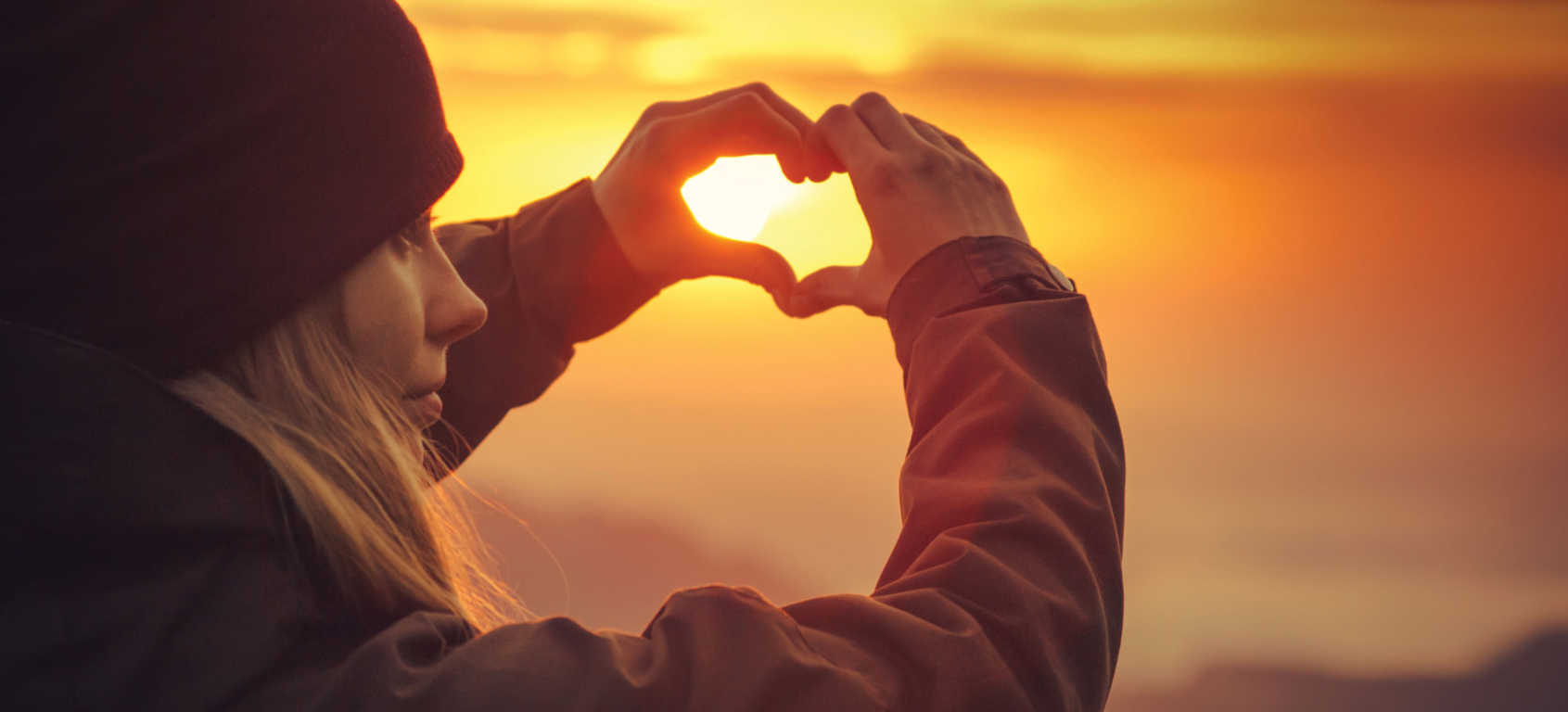 Women making a heart with her hands in front of an orange sunset in honor of May's Mental Health Awareness Month.