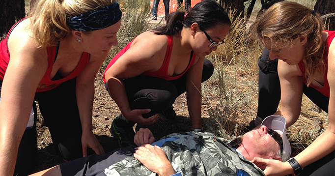 Team Wonder Women attempt to stabilize a mock patient with a laceration in the neck.
