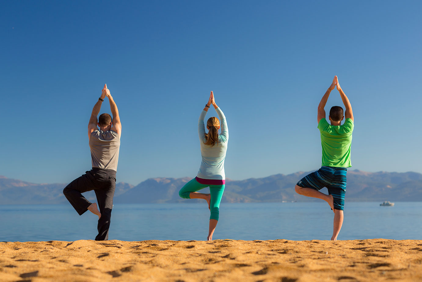 Three people doing yoga on a Lake Tahoe beach.