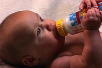 Picture of a baby feeding himself a bottle