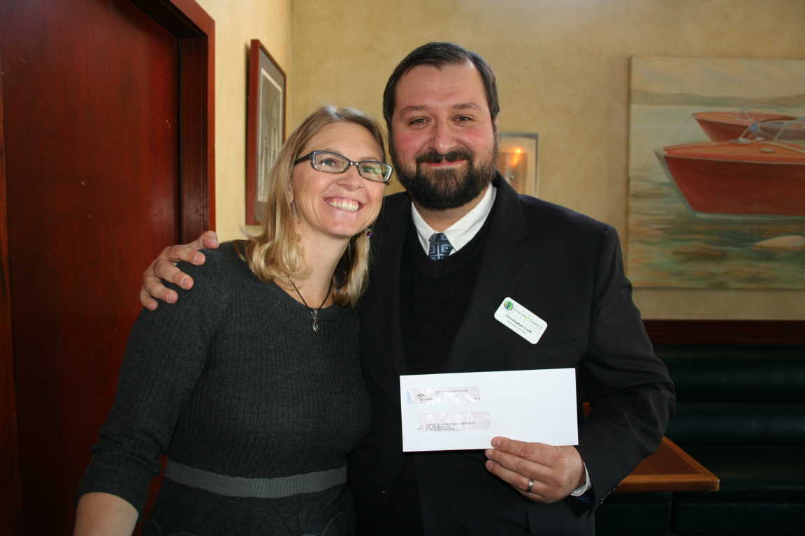 Christopher Croft, Executive Director of Tahoe Youth and Family Services, accepts a grant from Community Health Advisory Committee Chair Michelle Feeney, FNP for youth and family counseling programs.