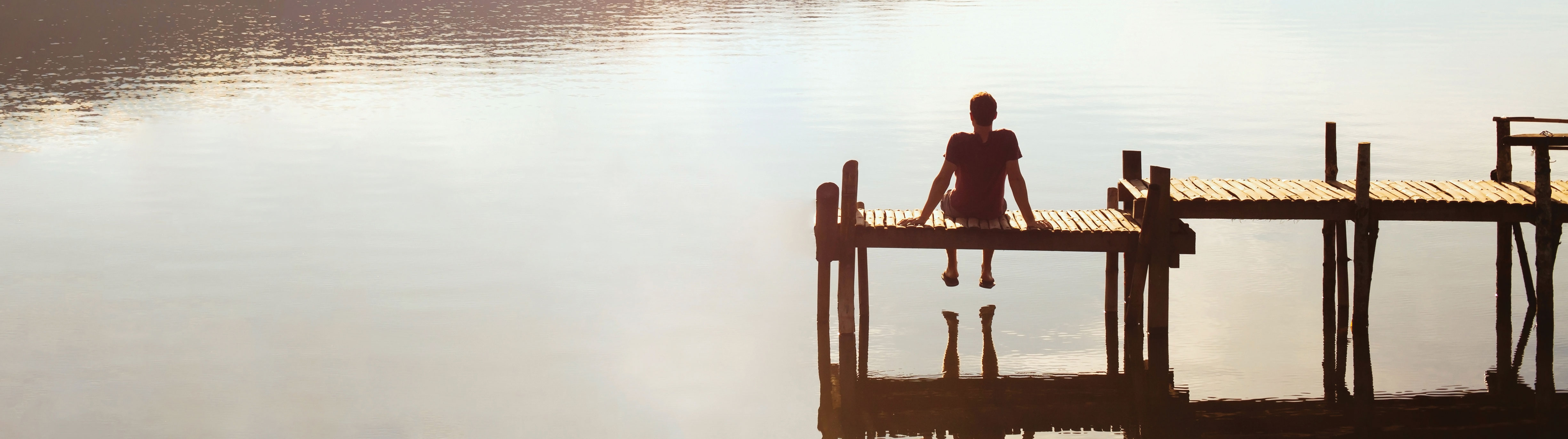 Man sits at the end of a dock overlooking lake.