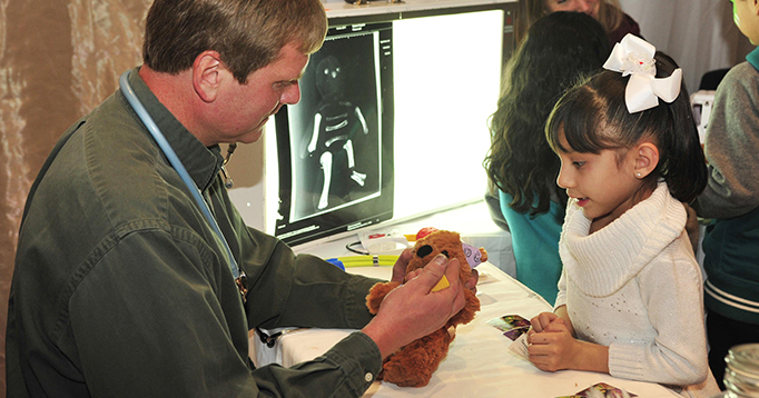 Dr. Orr takes a bear's vitals at the Teddy Bear Hospital
