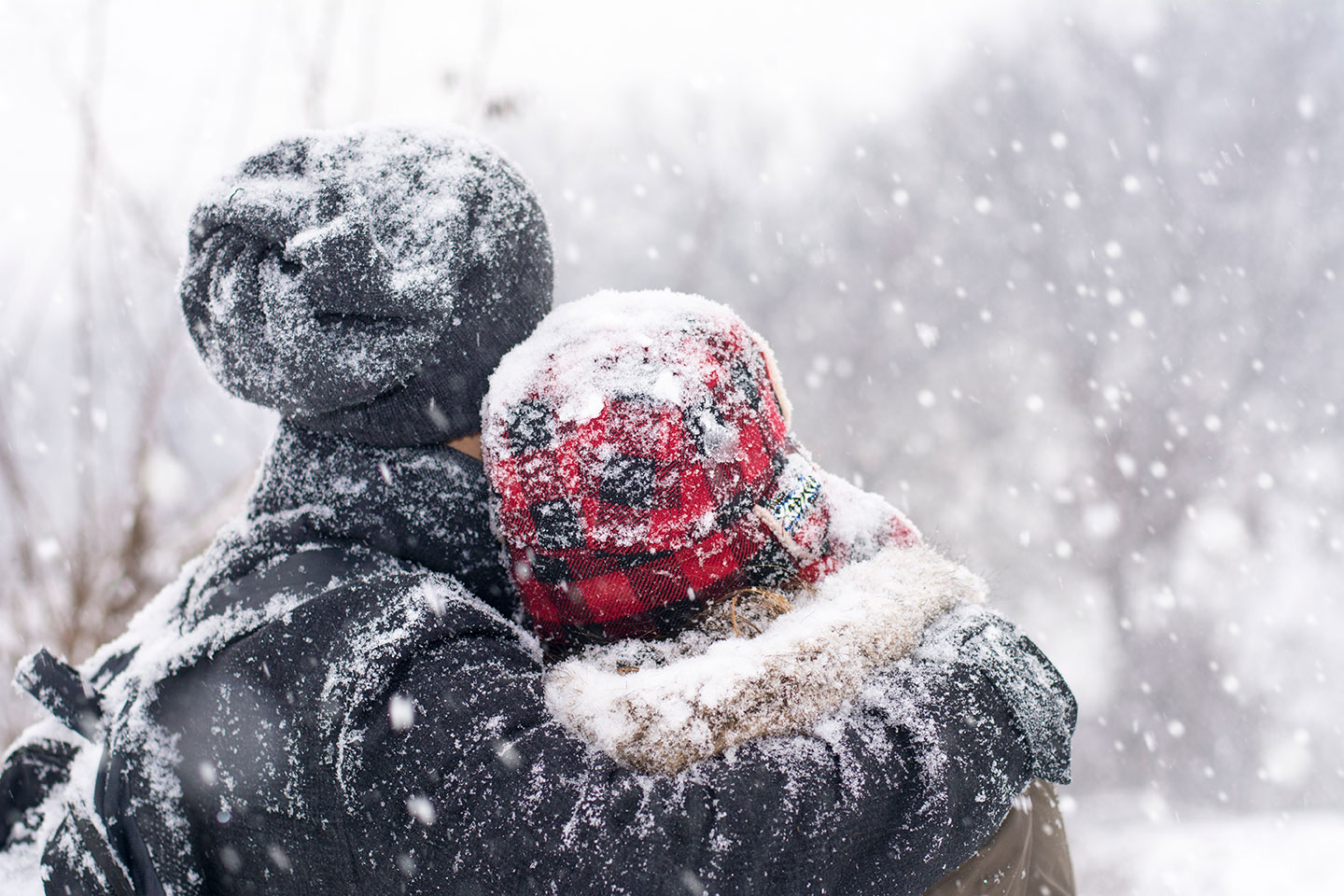 Man and woman standing in falling snow.