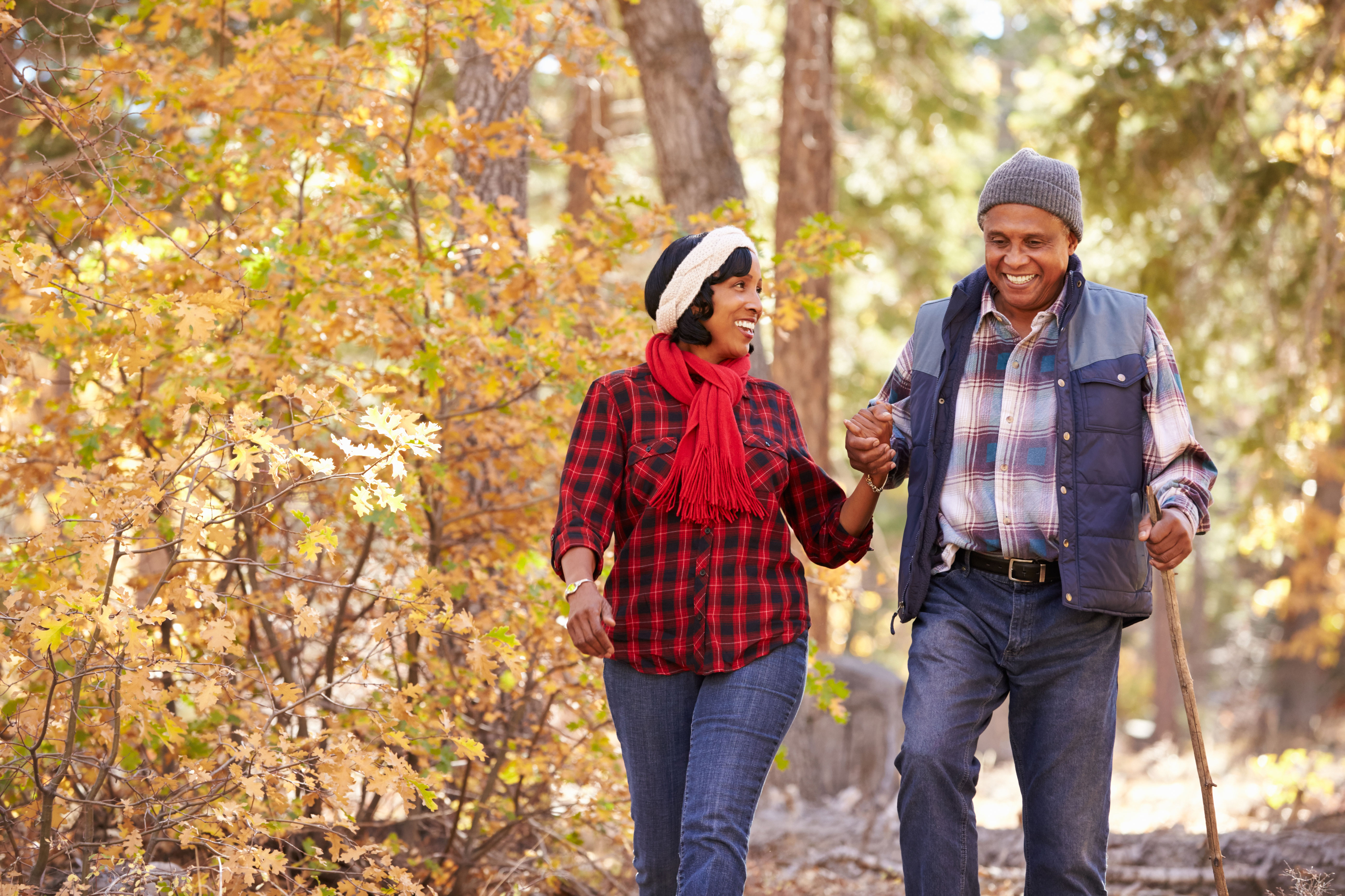 Couple walking through forest with fall foliage surrounding.