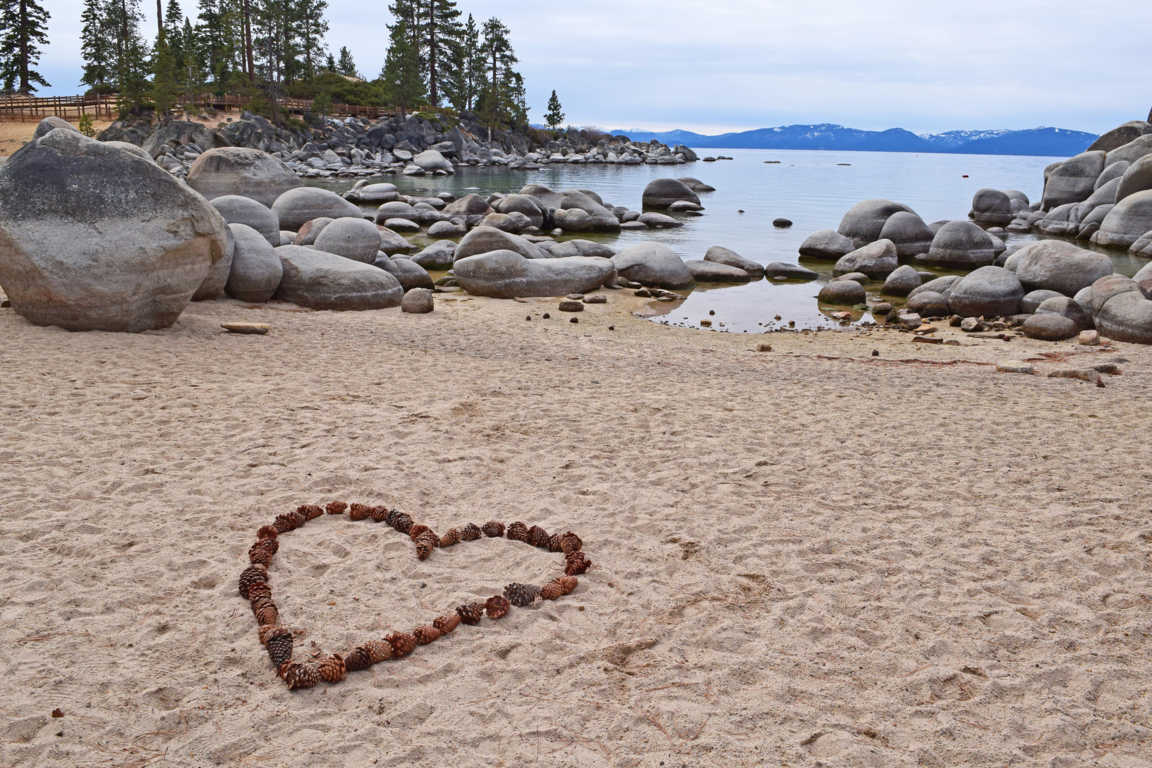 Pinecones in shape of a heart on a beach at Lake Tahoe.