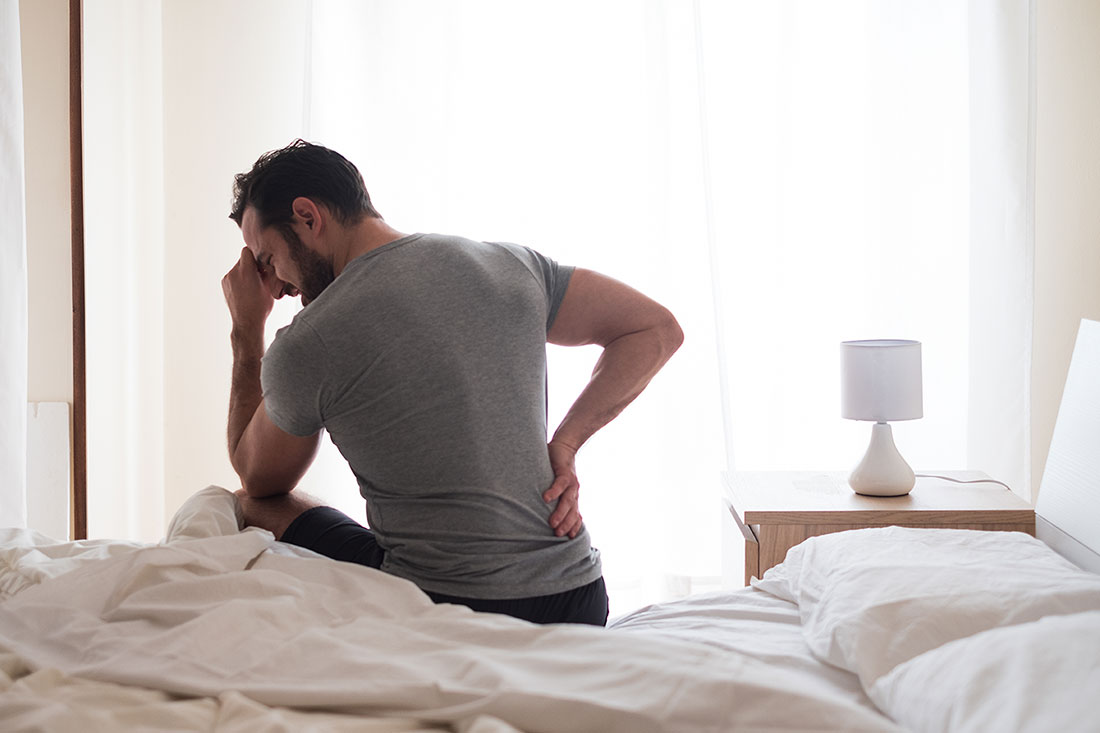 Man wakes up with sore lower back.