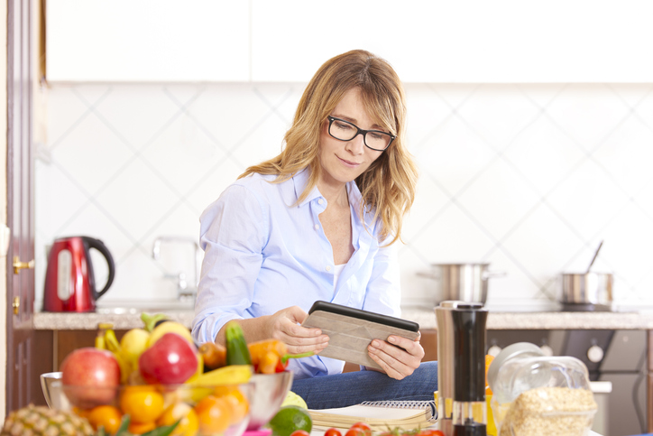Woman reviewing a recipe on her tablet in kitchen.